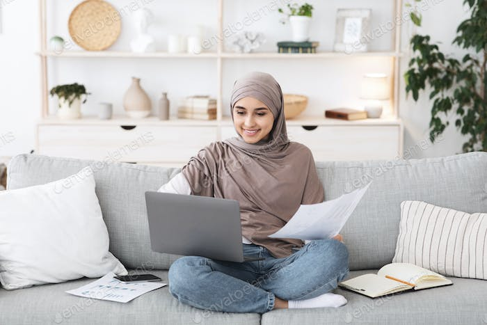 Home Office. Busy Arabic Woman Working With Laptop And Documents On Couch