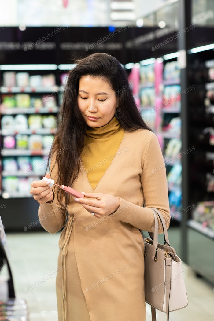 Young elegant Asian woman with handbag choosing new lip gloss in beauty shop