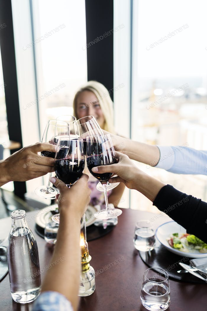 Cropped image of friends toasting with red wine in restaurant