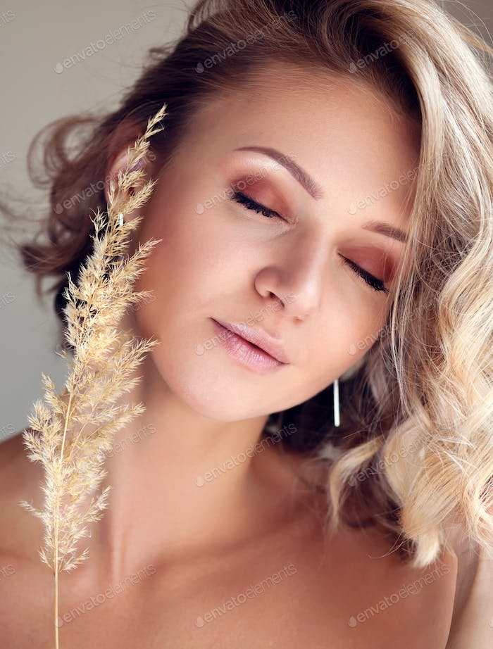 Glamorous portrait of a beautiful blonde woman with fresh daily makeup and a romantic wavy hairstyle