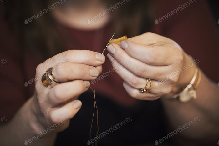 A woman using a needle threaded with cotton thread.