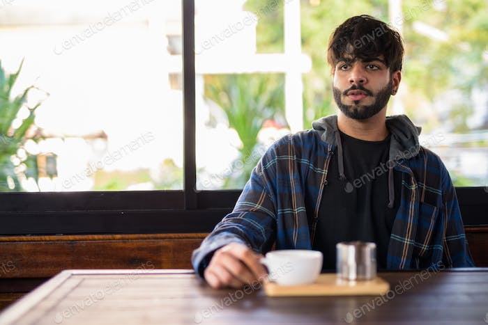 Young handsome bearded Indian hipster man thinking at the coffee shop