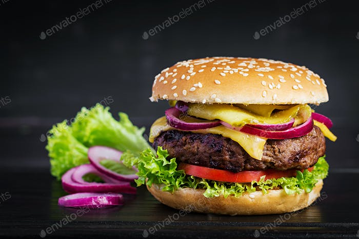 Big sandwich - hamburger burger with beef,  tomato, cheese, pickled cucumber and red onion.