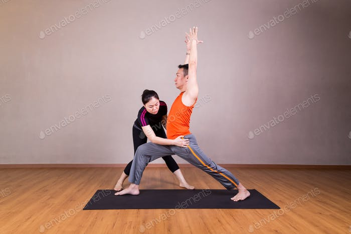 Yoga instructor correcting student performing Warrior 1 or Virab