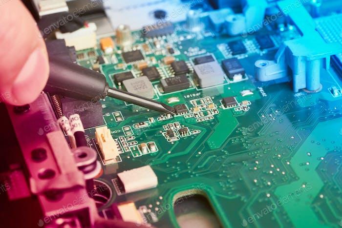 Man repairs computer. A service engineer in shirt repairs laptop, at white Desk
