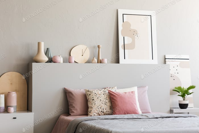 Poster on headboard of bed with pink cushions in grey bedroom in