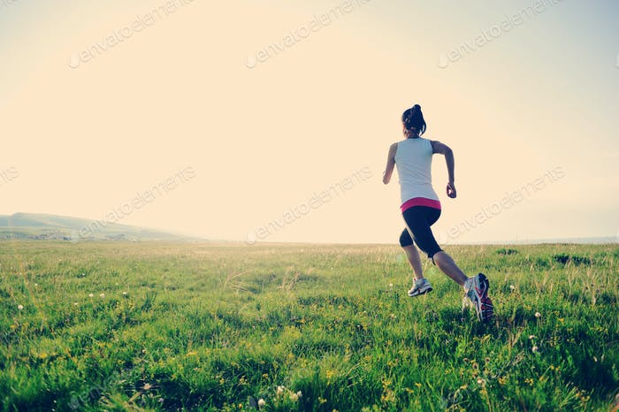 Runner athlete running on grass seaside