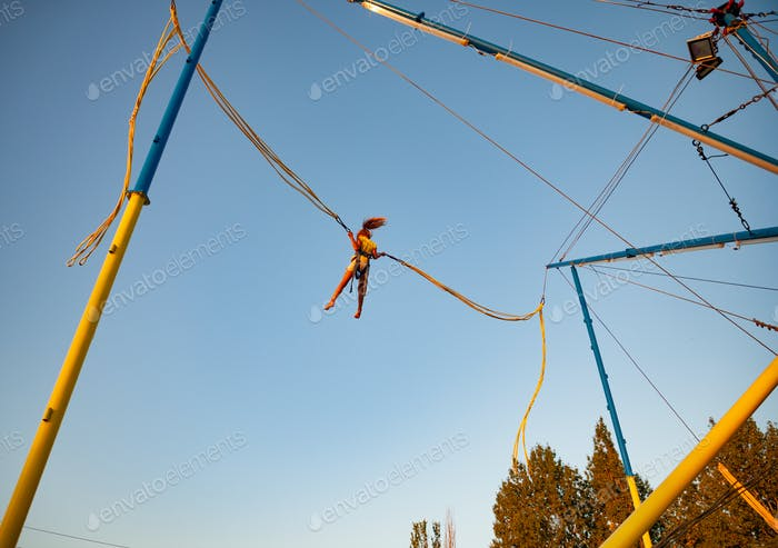 Little girl flies on elastic bands and jumps on a trampoline