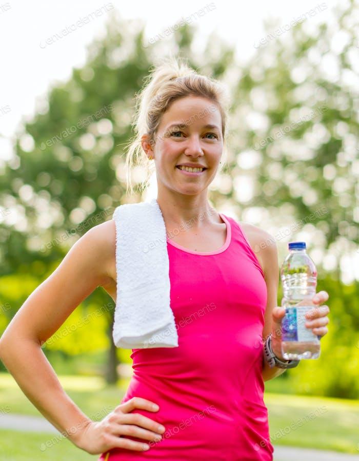 blonde Frau mit einer Wasserflasche und Handtuch