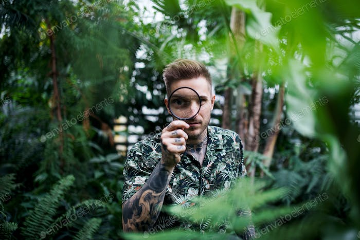 Young man with magnifying glass standing in botanical garden
