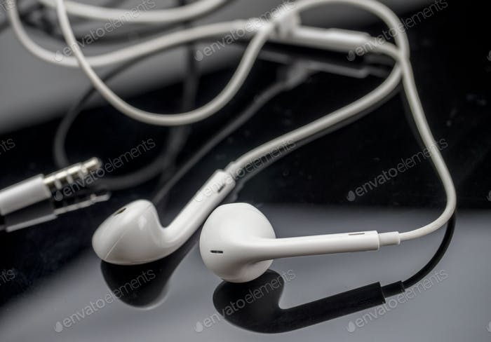 White headphones isolated on black background, conceptual image