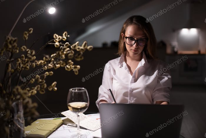 Young woman with glass of wine browsing laptop at home