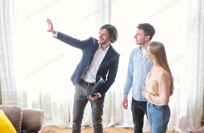 Millennial couple with real estate agent visiting house for sale