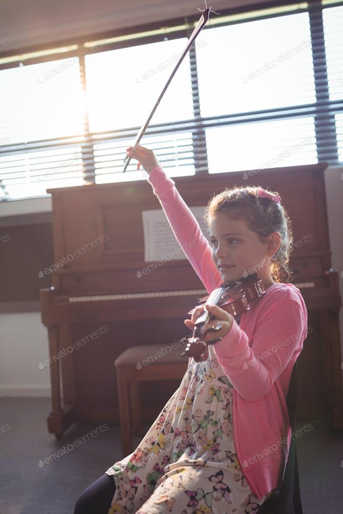 Cute girl rehearsing violin in music class