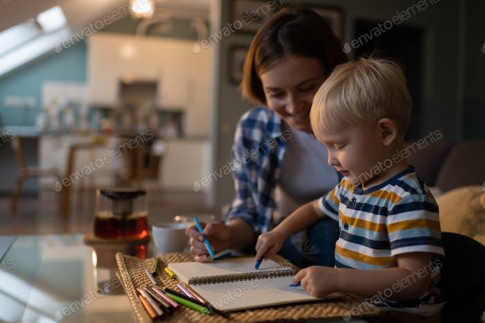 Kleiner Junge und weibliche Babysitter Zeichnung Bild mit Bleistiften zu Hause
