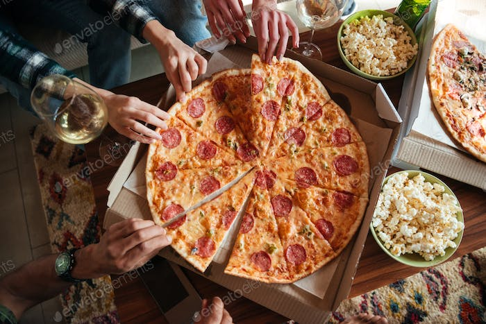 Top view of a group of friends eating big pizza