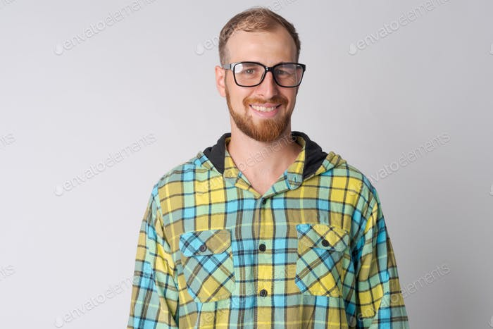 Portrait of happy young bearded hipster man with eyeglasses smiling