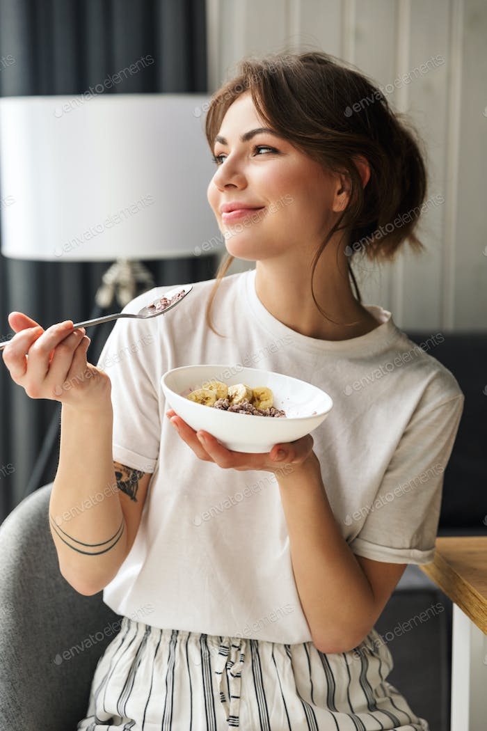 Photo of young smiling cute woman eating granola while having breakfast