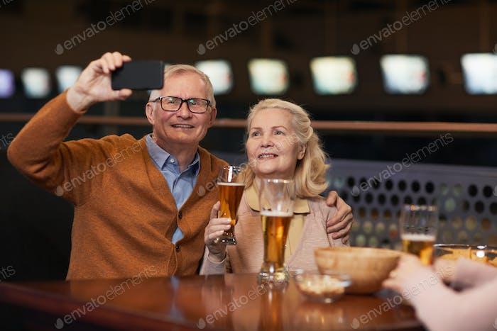 Senior Couple Taking Selfie in Bar
