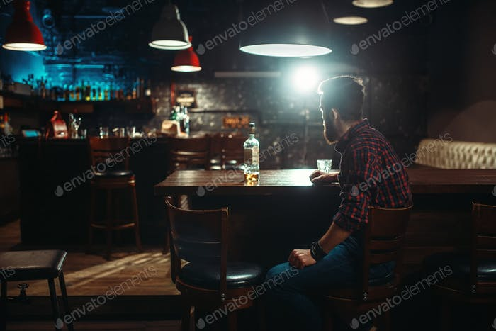 Smiling man sitting at the bar counter,