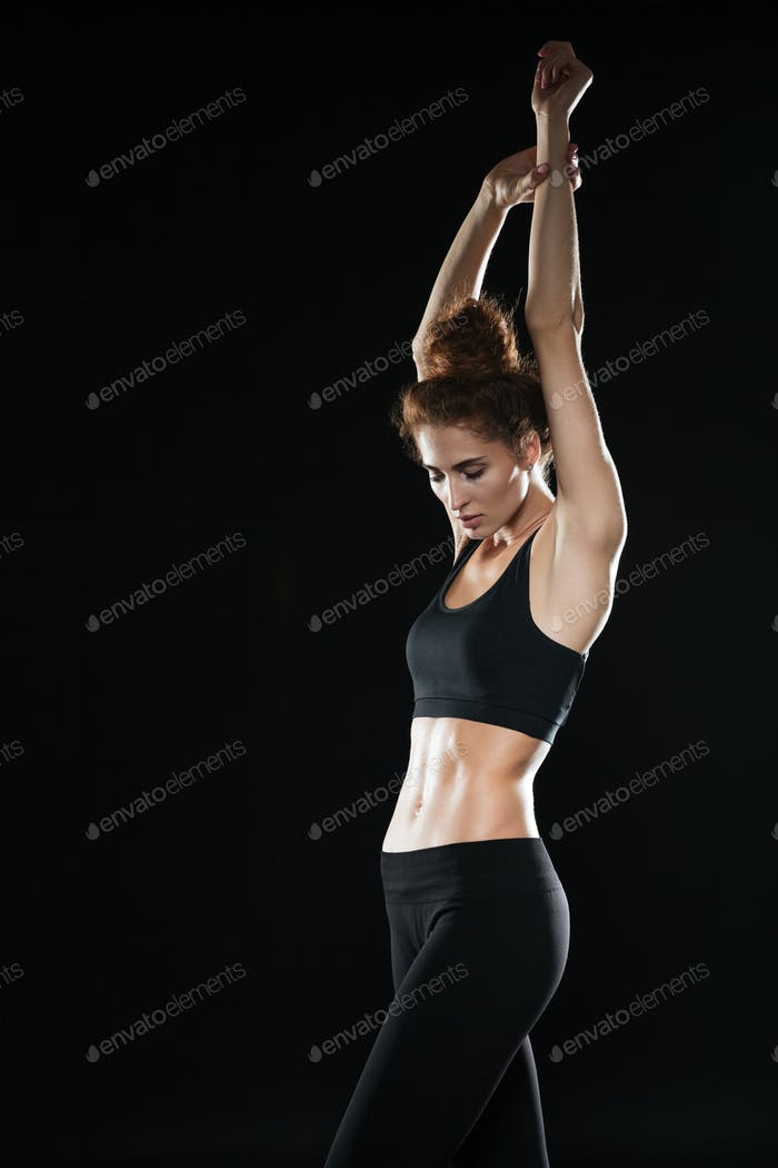 Vertical image of fitness woman holding hands overhead