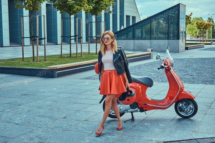 Stilvolle blonde Mädchen stehen in der Nähe klassischer italienischer Roller gegen einen Wolkenkratzer.