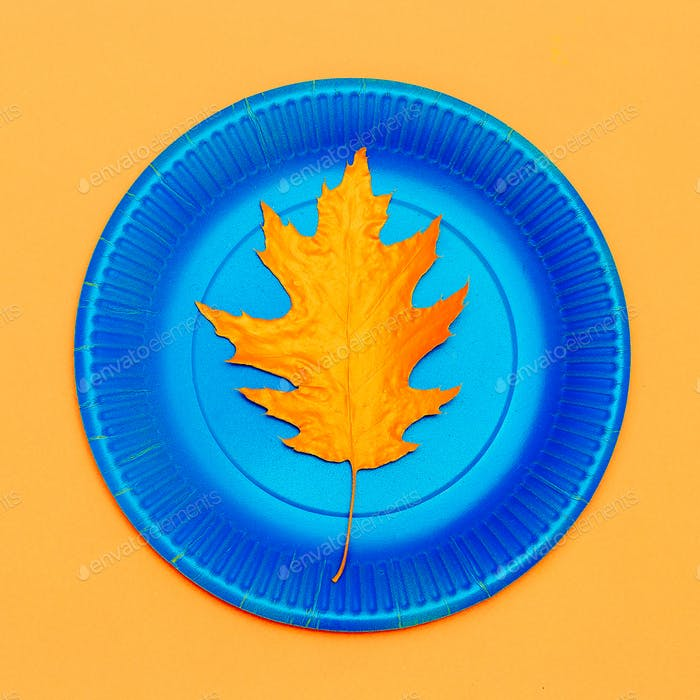 Art gallery. Autumn painted leaf on a plate Minimal