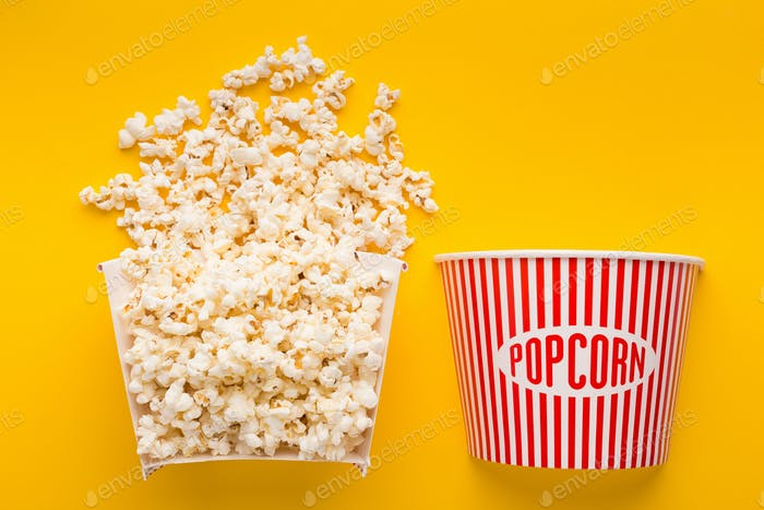 Popcorn bucket cut in half on yellow background