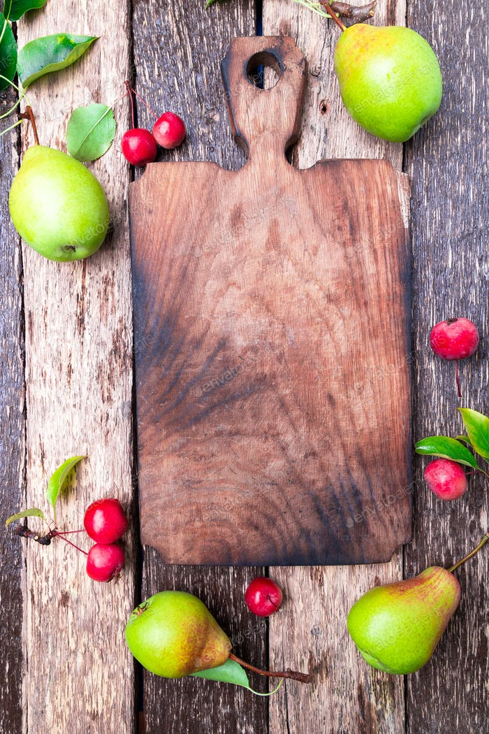Pear and small apple around empty cutting board on wooden rustic background.  Frame.