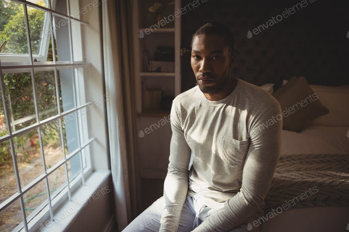 Portrait of serious man sitting on bed by window