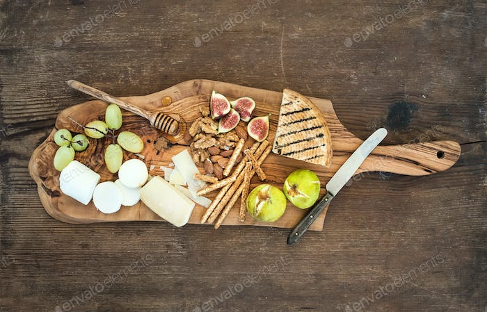 Wine appetizers set: cheese selection, honey, grapes, almonds, walnuts, bread sticks, figs