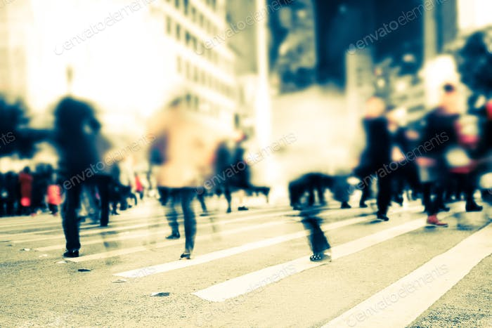 Blurred image of people moving on crosswalk at crowded city