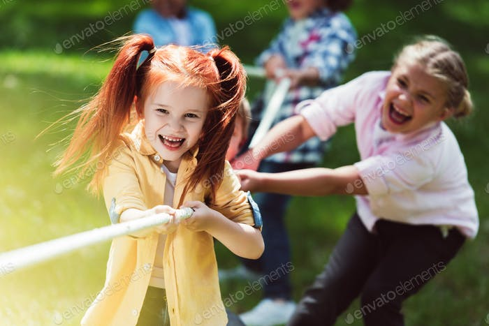 adorable cheerful girls playing tug of war in park