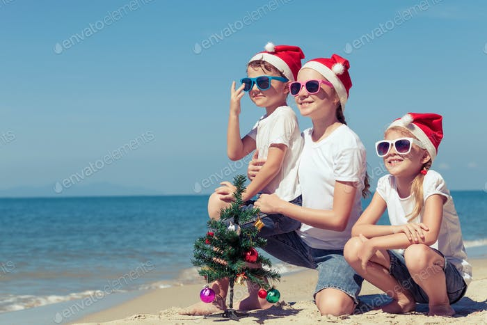 Three happy children  playing on the beach at the day time.