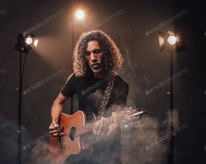 Hispanischer Musiker mittleren Alters emotional Gitarre in Bühnenlichtern spielen, umgeben von Rauch