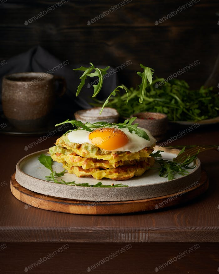 Homemade keto waffles with fried egg, flying arugula, mozzarella cheese. Levitation. Chaffles, keto