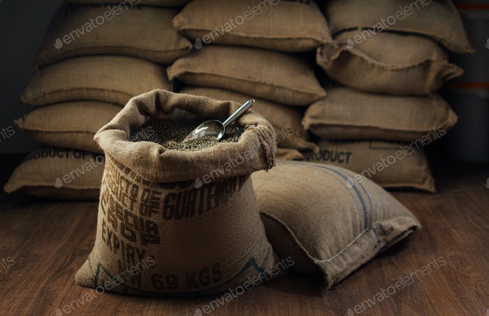 open bag full of raw coffee beans with metal scoop, in the background of the warehouse