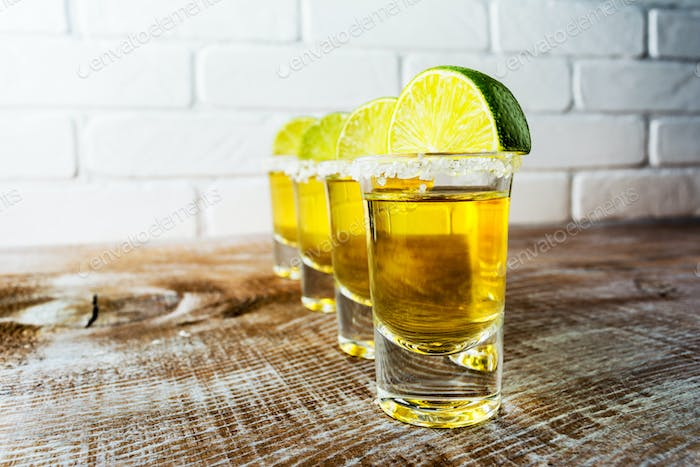 Tequila shots on the rustic wooden table and painted brick wall.