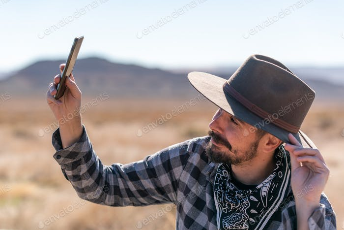 Cowboy with grey hat, moustache and checked shirt taking a selfie