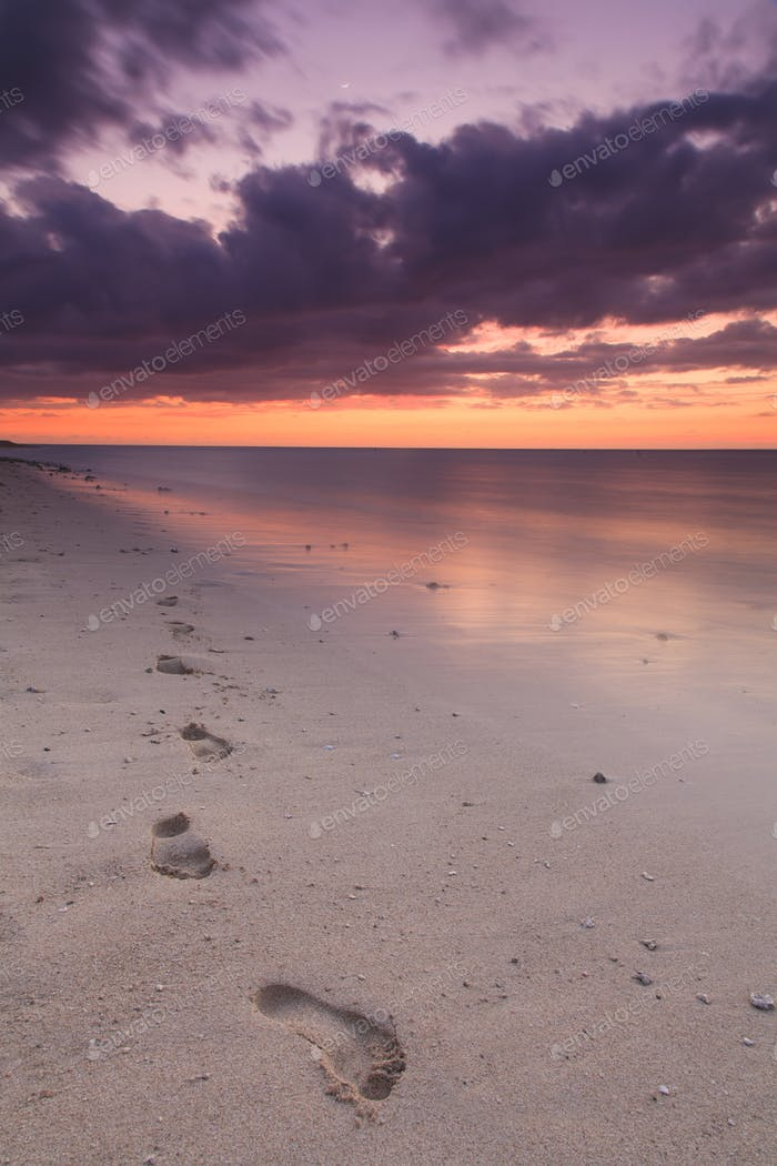 Footprints in the sand at sunset on the shore of a tropical isla