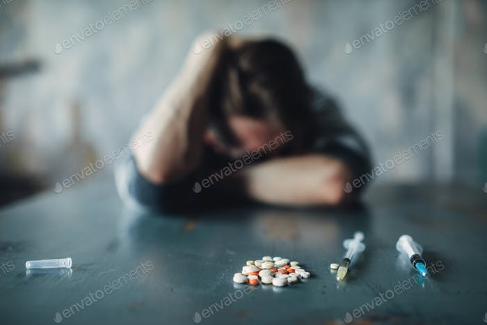 Male junkie at the table with drugs and syringe