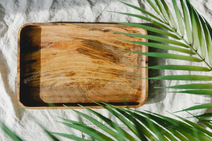 Wooden tray is made from mango tree on a linen cloth decorated palm leaf