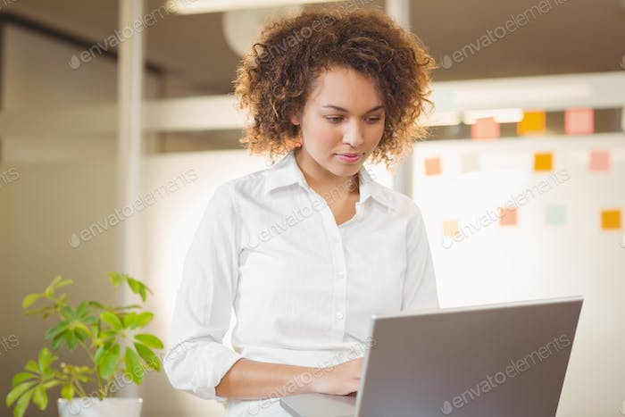 Serious businesswoman using laptop in office