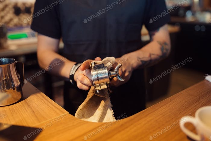 Barista at work in a coffee shop. Hands close up