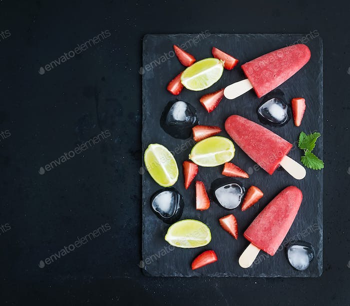 Strawberry and lime ice-creams or popsicles with fresh cut berries