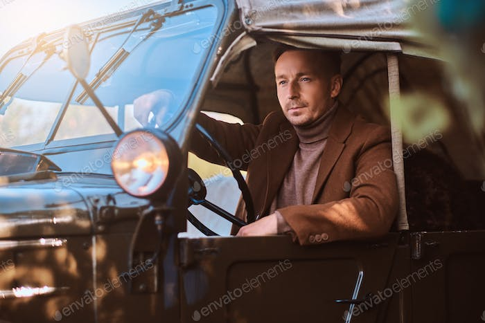 Handsome male elegantly dressed sit in the retro military machine.