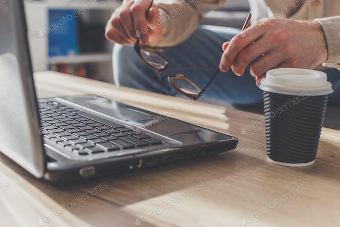 Man putting up eyeglasses on laptop to make a short break, tired after long work or getting nervous.