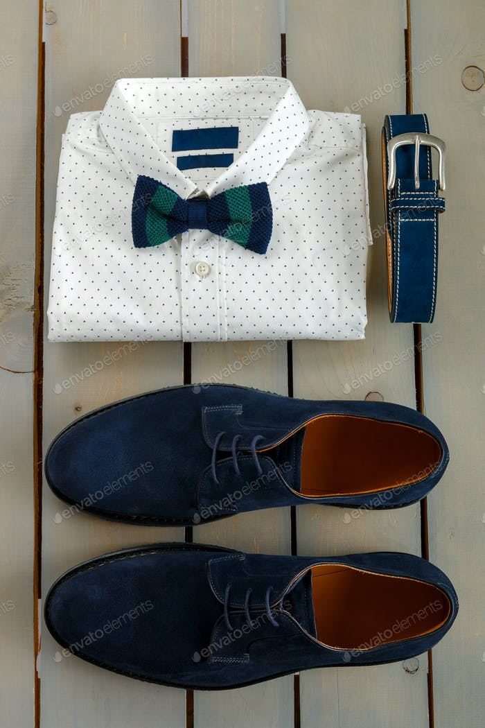 Top view of gentlemanly set. Mens outfits, white polka-dot shirt with with bow tie, blue belt