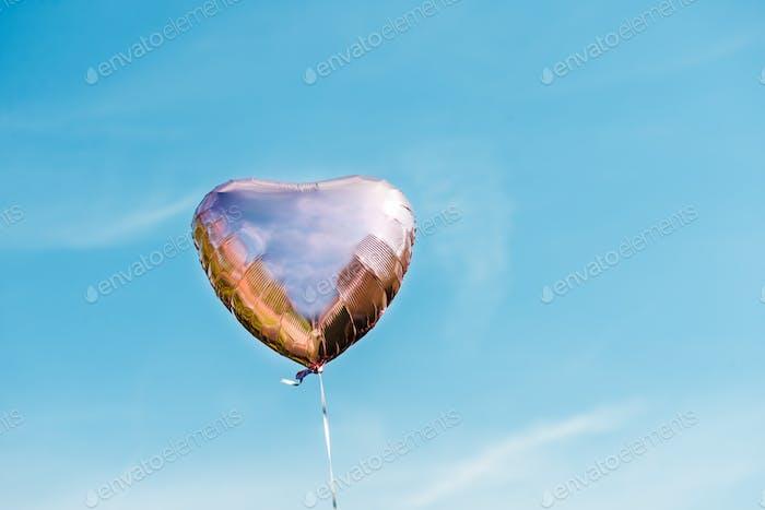 Heart shaped ballon on the sky background