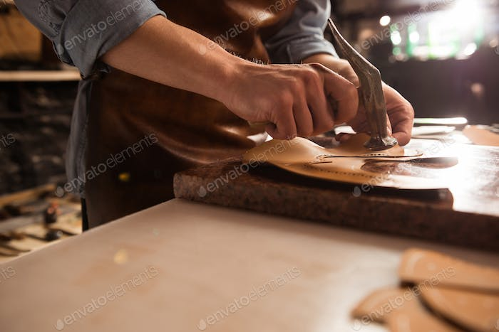 Close up of a shoemaker man working with leather